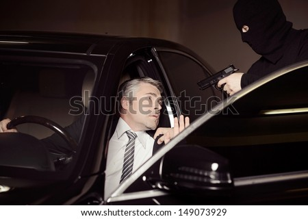 Attacking a businessman. Men in black balaclava holding gun and aiming a shocked mature businessman sitting on the front seat of a car - stock photo