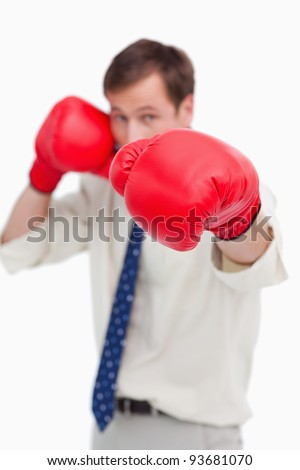 Attacking businessman with boxing gloves against a white background
