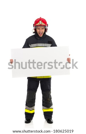 Attention! Read this. Shouting fireman in red helmet standing and holding placard. Full length studio shot isolated on white. - stock photo
