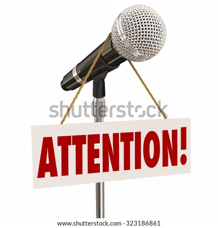Attention word on a hnaging sign over a microphone urging you to listen or hear an important announcement, news or speech - stock photo