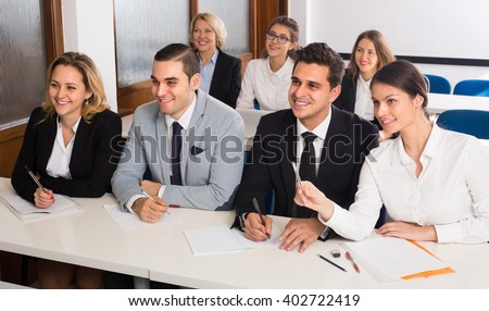 Attentive adult business students sitting at the desks in classroom. Selective focus - stock photo