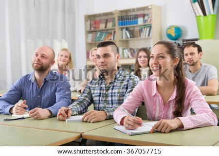 Attentive adult students industriously writing down summary in a classroom  - stock photo