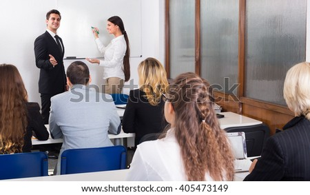 Attentive adult students with teacher in classroom at business training  - stock photo