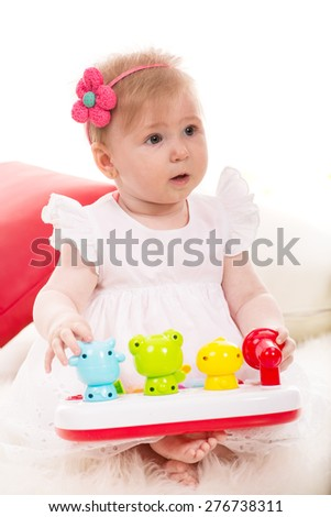 Attentive baby girl looking away and playing with toys - stock photo
