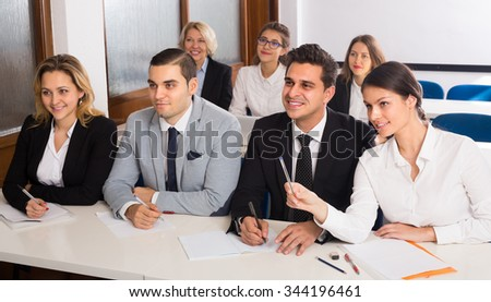Attentive business students at the desks in classroom. Selective focus - stock photo