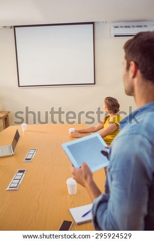 Attentive business team following a presentation in the office - stock photo