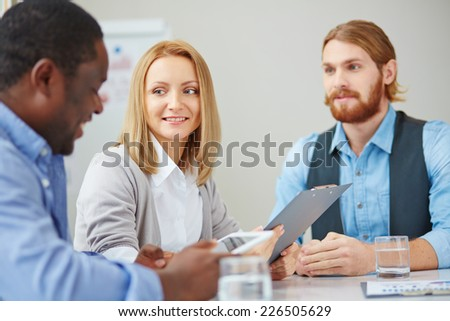 Attentive businesswoman looking at one of male colleagues at meeting - stock photo