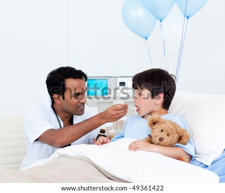 Attentive doctor giving medicine to a little boy at the hospital - stock photo