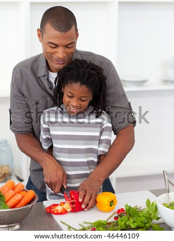 Attentive father helping his son cut vegetables in the kitchen - stock photo