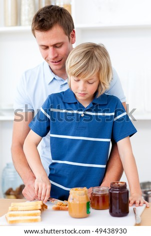 Attentive father helping his son prepare the breakfast in the kitchen - stock photo
