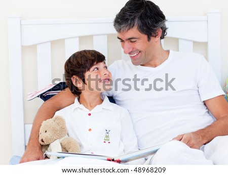 Attentive father reading with his son sitting on a bed - stock photo