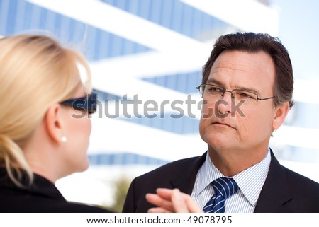 Attentive Handsome Businessman in Suit and Tie Listens to Female Colleague Outdoors. - stock photo