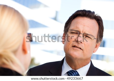 Attentive, Handsome Businessman in Suit and Tie Talking with Female Colleague Outdoors. - stock photo