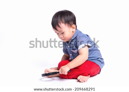 Attentive little boy researching using magnifier isolated on white background