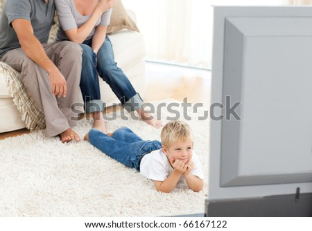 Attentive little boy watching television lying on the floor at home