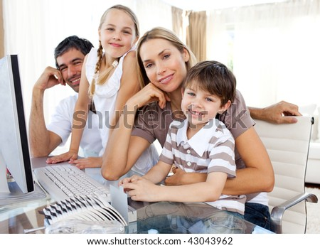 Attentive parents and their children using a computer at home - stock photo