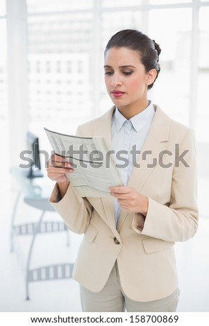 Attentive smart brown haired businesswoman reading a newspaper in bright office