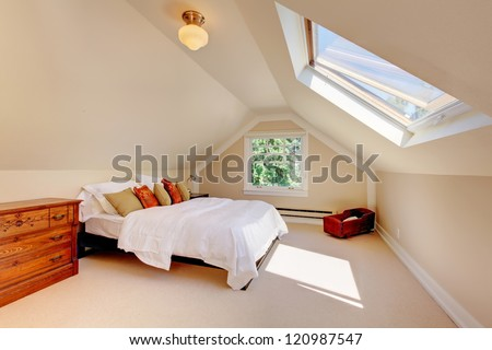 Attic modern bedroom with white bed and skylight and beige walls and carpet.