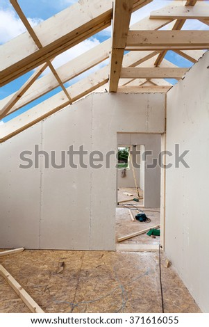 Attic room under construction with gypsum plaster boards. Roofing Construction Indoor. Wooden Roof Frame House Construction. - stock photo