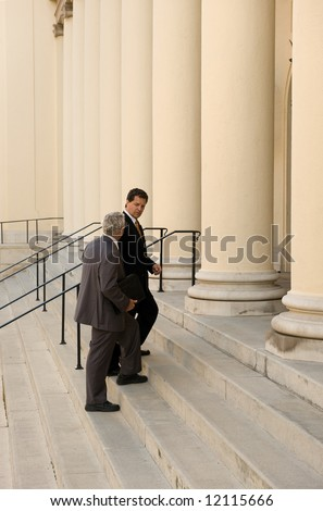 Attorney and client walking up the steps of a courthouse - stock photo