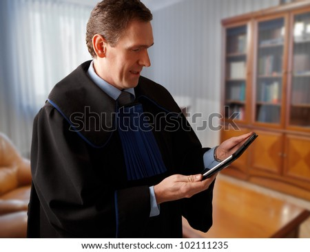 Attorney wearing classic gown with tablet in his office - stock photo