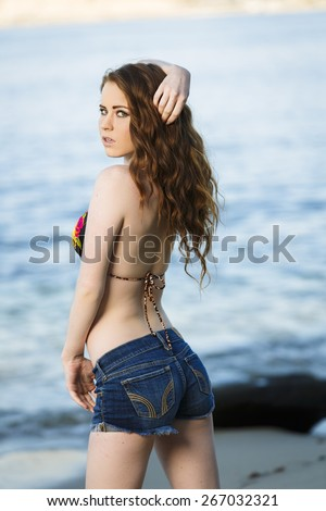 Attracted young girl posing in cut off denim shorts and bikini top - stock photo