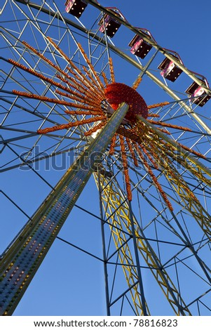 attraction - a Ferris wheel on the background of clear blue sky - stock photo
