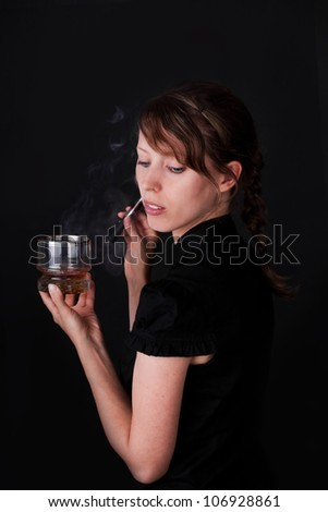 attractiv caucasion woman smoking e-cigarette and holding a drink - stock photo