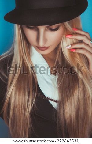 Attractive adult blonde woman with closed eyes in studio - stock photo