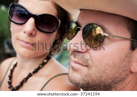 Attractive adult couple wearing fashionable sunglasses - stock photo