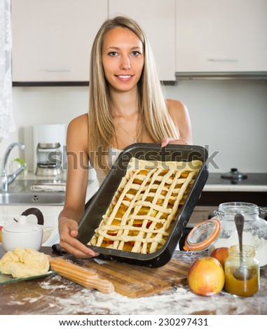 Attractive adult girl cooking apple pie in kitchen at home  - stock photo