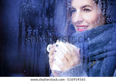 attractive adult woman drinking coffee and looking out of the window on rainy day, close up portre in winter time