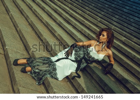 Attractive adult woman lying on stairs - stock photo
