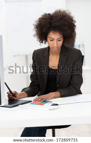 Attractive African American businesswoman or student hard at work at her desk taking notes on tablet with a stylus as she reads a report - stock photo