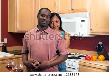 Attractive african american couple standing and hugging in their kitchen with a neutral expression on their faces.