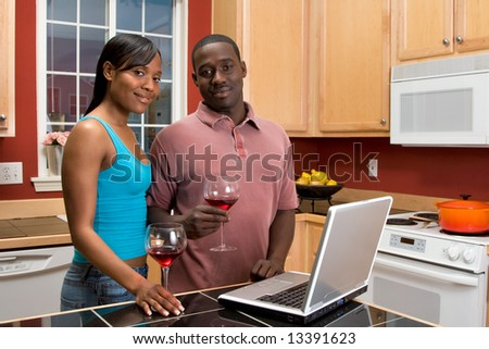 Attractive African American couple, with neutral expressions, standing in a kitchen, holding wine glasses, while using a laptop.  Horizontally framed shot with the man and woman looking at the camera.