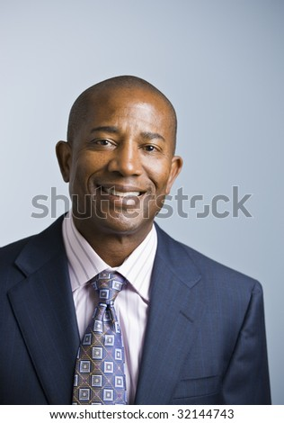 Attractive African American headshot dressed in a suit and tie, facing the camera. vertical - stock photo
