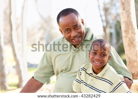 Attractive African American Man and Child Having Fun in the Park. - stock photo