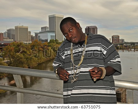 Attractive African American man wearing chains pointing ahead while leaning against the bars of the Belle Isle bridge in Richmond, Virginia. - stock photo