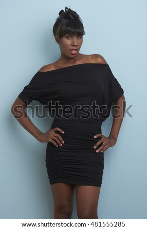 Attractive African American model wearing casual clothing in studio setting.