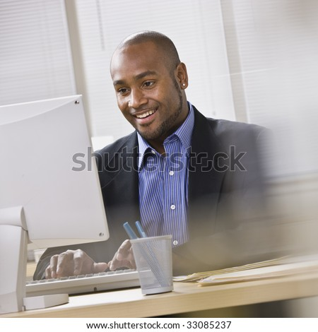 Attractive African American smiling at computer, while sitting at a desk typing on keyboard. Square. - stock photo
