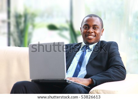 Attractive African American smiling at computer, while sitting at a desk typing on keyboard. Square - stock photo