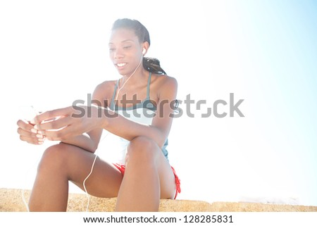 Attractive african-american woman against a blue sky, having a break from exercising and listening to music with her ear phones on a sunny day. - stock photo