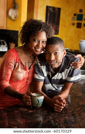 Attractive African-American woman and teen in kitchen