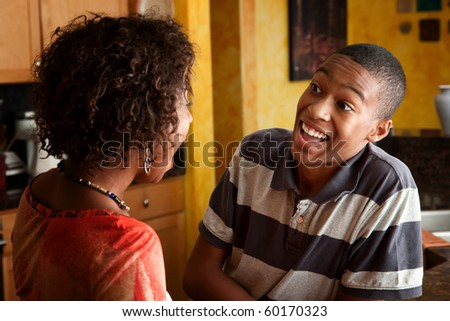 Attractive African-American woman and teen laugh in kitchen - stock photo