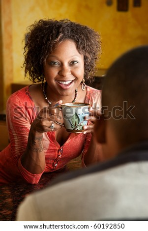 Attractive African-American woman and young man in kitchen