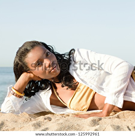 Attractive african american woman laying down on a golden sand beach by the sea shore, relaxing and sunbathing during a summer day. - stock photo