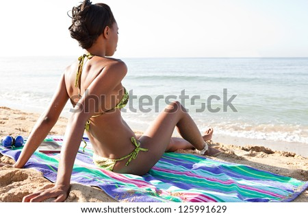 Attractive african american woman on vacation sitting on a towel on a golden beach, contemplating the sea while on vacation, with a blue sky. - stock photo