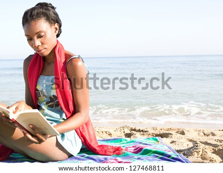 Attractive african-american woman reading a book while sitting on a stripy towel on a golden sand beach while on vacation. - stock photo
