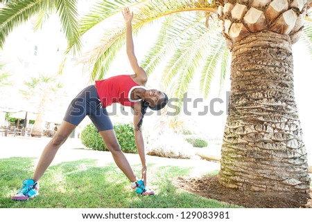 Attractive african american woman stretching after doing sport in the city under a palm tree, training for fitness. - stock photo